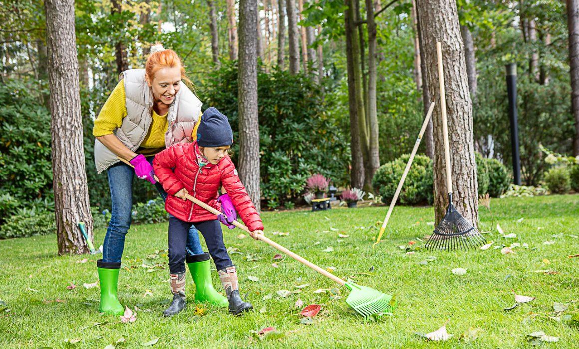 kobieta i dziecko grabią liście